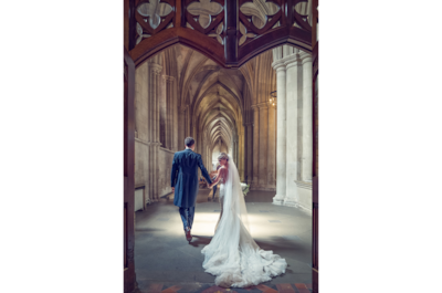 brent-kirkman-sony-alpha-9-newly-wed-couple-walk-through-impressive-archway-hand-in-hand
