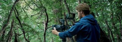Imagine cu un bărbat folosind o cameră atașată la un microfon extern și la un monitor extern, cu frunziș în fundal
