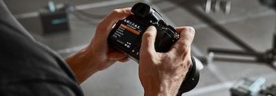 Vedere cu partea din spate a camerei ținute în mână, afișând un ecran de meniu pe monitorul camerei