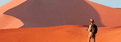 Imagine cu bărbat care se uită în partea opusă camerei, cu dune de nisip de culoare roșie în fundal