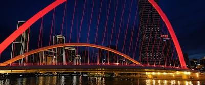 Imagine nocturnă cu un peisaj urban, cu un pod iluminat de culoare roșie în prim-plan
