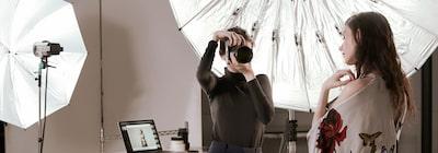 Imagine cu o fotografă și un model feminin într-un studio de fotografie